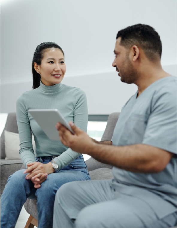 Photo of a young woman and a male nurse discussing at-home caregiving pricing plans