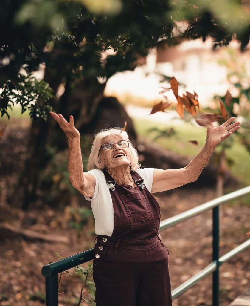 Photo of an elderly woman smiling and throwing autumn leaves in the air
