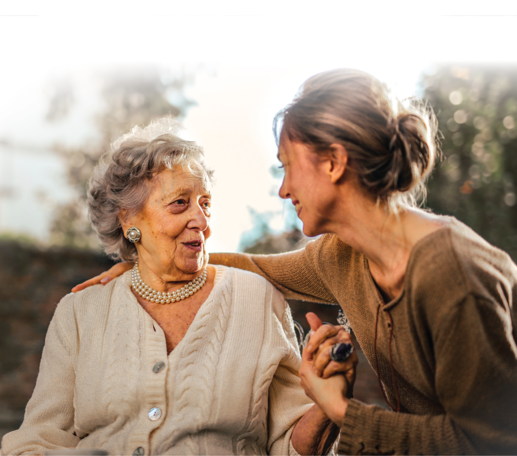 Photo of a woman and her grandmother hugging and smiling at each other